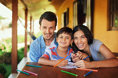 Buy stock photo Portrait of a couple and their son coloring in together outdoors