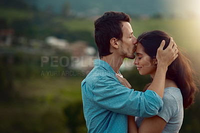 Buy stock photo Cropped shot of an affectionate young couple sharing a loving moment while standing outdoors