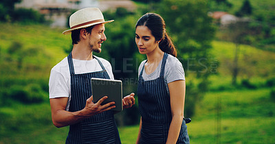 Buy stock photo Shot of a young couple using a digital tablet together while working in a garden