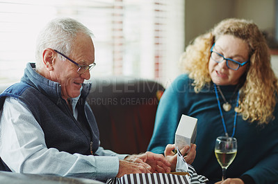 Buy stock photo Cropped shot of a senior man opening a gift on his birthday