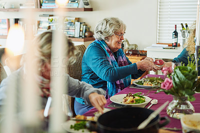 Buy stock photo Cropped shot of an affectionate family enjoying lunch during their get together