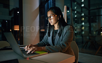 Buy stock photo Shot of a young businesswoman using her laptop while working late at the office