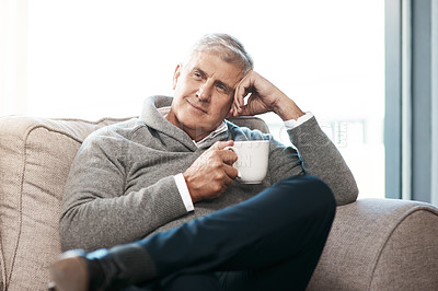 Buy stock photo Cropped shot of a handsome mature man enjoying a coffee while looking thoughtful on the sofa at home