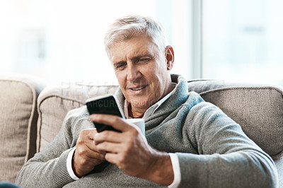 Buy stock photo Cropped shot of a handsome mature man enjoying a coffee while reading a text on the sofa at home