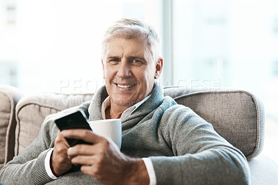 Buy stock photo Cropped portrait of a handsome mature man enjoying a coffee while reading a text on the sofa at home
