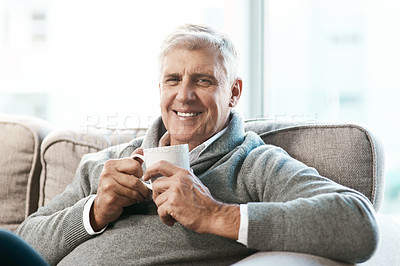 Buy stock photo Cropped portrait of a handsome mature man enjoying a coffee while relaxing on the sofa at home