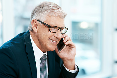 Buy stock photo Cropped shot of a handsome mature businessman making a phonecall while working in the office