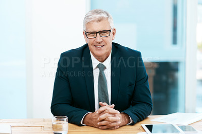 Buy stock photo Cropped portrait of a handsome mature businessman sitting at his desk in the office