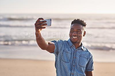 Buy stock photo Shot of a happy young man taking a selfie on his mobile phone at the beach