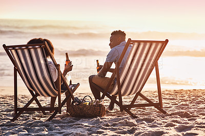Buy stock photo Shot of a happy young couple relaxing on chairs and having drinks at sunset on the beach