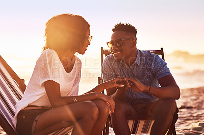 Buy stock photo Shot of an affectionate young couple relaxing on chairs at the beach