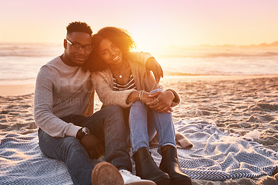 Buy stock photo Shot of a happy young couple relaxing on a blanket during sunset at the beach