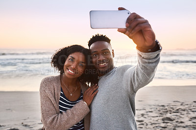 Buy stock photo Shot of a happy young couple taking selfies on a mobile phone at the beach