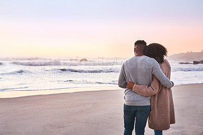 Buy stock photo Rearview shot of a happy young couple standing by the water's edge and looking at the view of the ocean