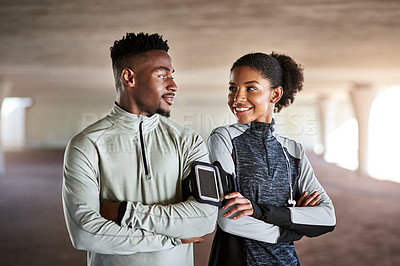 Buy stock photo Cropped shot of a young couple listening to music while exercising outdoors in the city