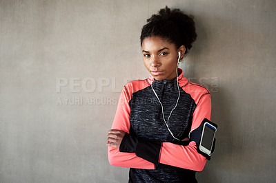 Buy stock photo Cropped portrait of an attractive young woman listening to music while exercising outdoors in the city