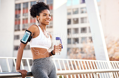 Buy stock photo Cropped shot of an attractive young woman taking a break for some water during her workout in the city