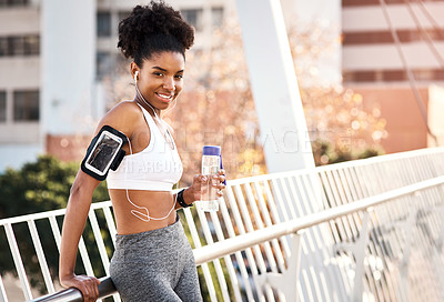 Buy stock photo Cropped portrait of an attractive young woman taking a break for some water during her workout in the city