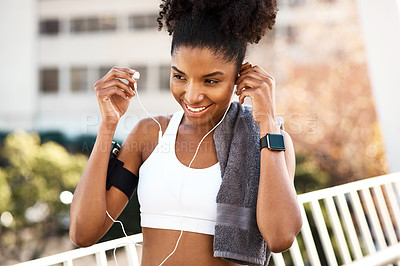 Buy stock photo Cropped shot of an attractive young woman listening to music while exercising outdoors in the city