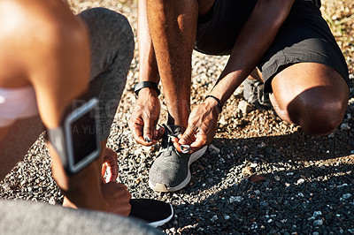 Buy stock photo High angle shot of an unrecognizable young couple fastening their shoelaces before beginning their run
