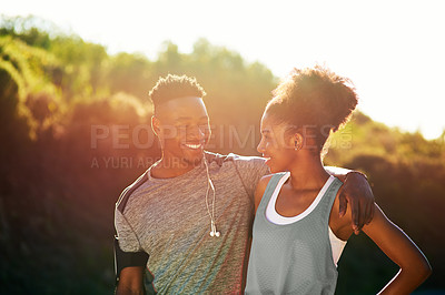 Buy stock photo Cropped shot of a young athletic couple listening to music while exercising outdoors