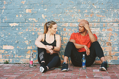 Buy stock photo Shot of two young people taking a break after exercising