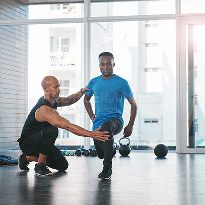 Buy stock photo Shot of a man working out with his trainer