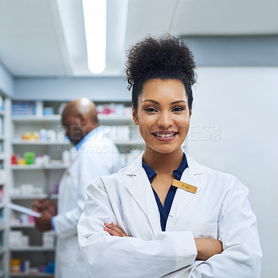 Buy stock photo Cropped shot of a female pharmacist in a pharmacy with her colleague in the background