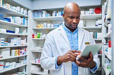Buy stock photo Shot of a pharmacist using a digital tablet while working in a chemist