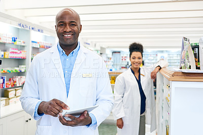Buy stock photo Shot of a male pharmacist at work with his colleague standing in the background