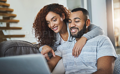 Buy stock photo Shot of a young man using his laptop while his girlfriend embraces him from behind
