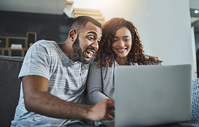 Buy stock photo Cropped shot of an affectionate young couple using a laptop at home
