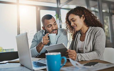 Buy stock photo Shot of a young couple using a digital tablet while planning their budget together at home