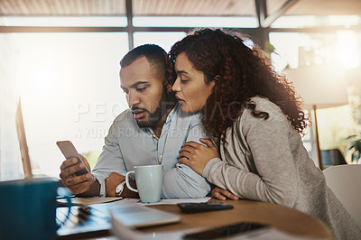 Buy stock photo Shot of a young couple using a cellphone while planning their budget together at home