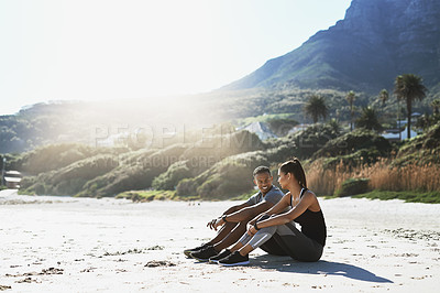 Buy stock photo Shot of a sporty young couple taking a break while exercising at the beach