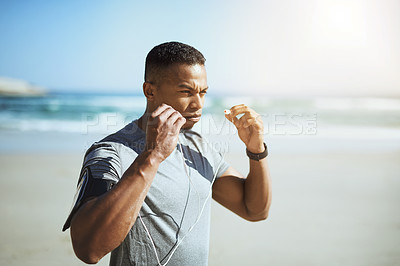 Buy stock photo Shot of a sporty young man listening to music while exercising outdoors