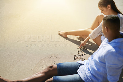 Buy stock photo Shot of a young couple writing in the sand while relaxing at the beach