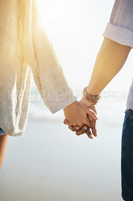 Buy stock photo Rearview shot of a young couple holding hands at the beach