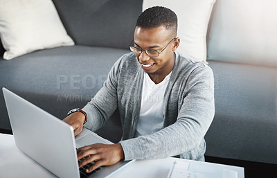 Buy stock photo Shot of a happy young man using a laptop while relaxing at home