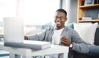 Buy stock photo Portrait of a young man having coffee and using a laptop while relaxing at home