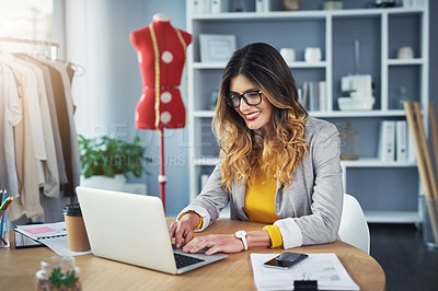 Buy stock photo Shot of a young woman using a laptop in her design studio