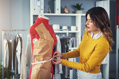 Buy stock photo Shot of a young woman taking measurements on a mannequin in a design studio