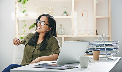 Buy stock photo Shot of a young businesswoman looking thoughtful while working in an office