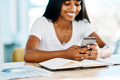 Buy stock photo Shot of a young student using a mobile phone at her desk