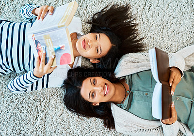 Buy stock photo High angle shot of two young women lying on the floor and reading books at university