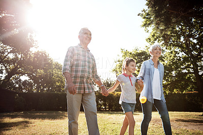 Buy stock photo Shot of an adorable little girl going for a walk with her grandparents in the park