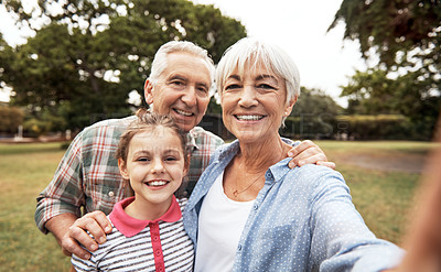 Buy stock photo Shot of an adorable little girl taking a selfie with her grandparents in the park