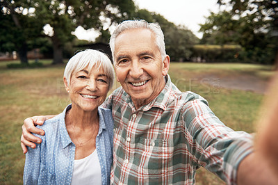 Buy stock photo Shot of a senior couple taking a selfie together in the park
