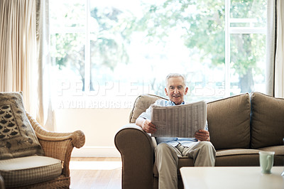 Buy stock photo Cropped shot of a senior man reading the paper while sitting on the sofa at home