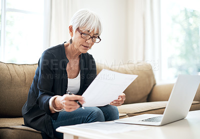 Buy stock photo Cropped shot of a senior woman going through her finances while sitting on the sofa at home
